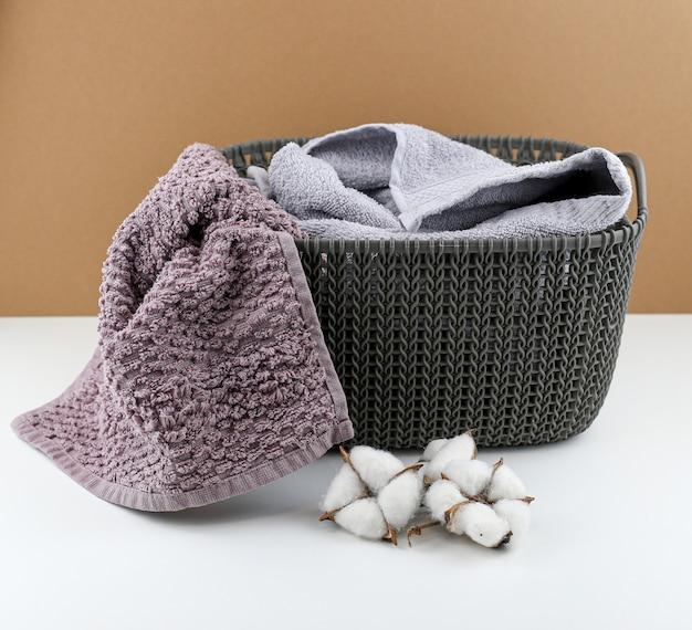 Cesto della biancheria con asciugamani e fiore di cotone