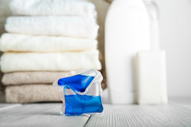 Capsule per bucato. gel per bucato in capsule e asciugamani di close-up.