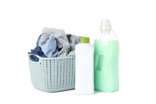 Detersivo e canestro di lavanderia con i vestiti isolati su bianco