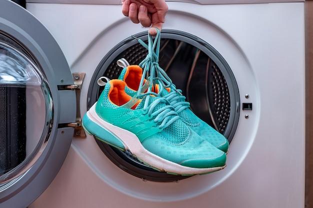 Scarpe sporche di sport della lavanderia in una lavatrice