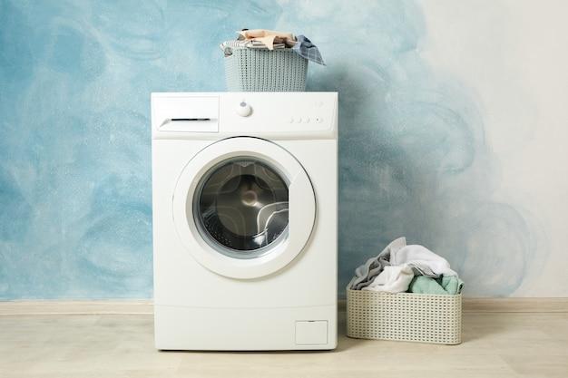 Lavanderia con lavatrice contro la parete blu