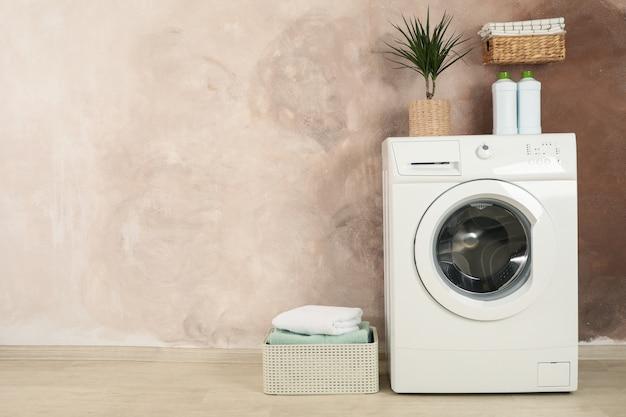 Lavanderia con lavatrice contro la parete marrone