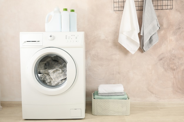 Lavanderia con lavatrice contro la parete marrone chiaro