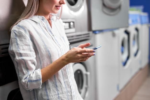 Lavanderia, donna sorridente con telefono in mano, lavare i vestiti tramite app. la giovane femmina caucasica ritagliata è pronta a lavare i vestiti