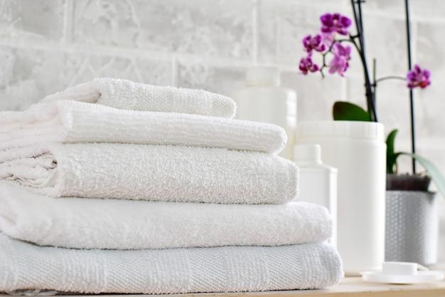 Biancheria, contenitori bianchi per la pulizia di prodotti mockup e una pila di panni bianchi