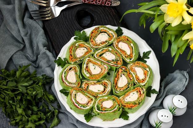 Rotolo di lavash con bastoncini di granchio, spinaci, prezzemolo e carote in stile coreano su un piatto su uno sfondo scuro, orientamento orizzontale, primo piano, vista dall'alto