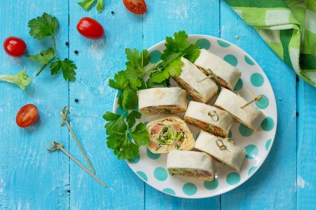 Rotolo di lavash con formaggio di pesce rosso e lattuga iceberg sul tavolo festivo vista dall'alto flat lay