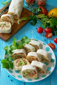 Rotolo di lavash con formaggio di pesce rosso e lattuga iceberg sul tavolo festivo