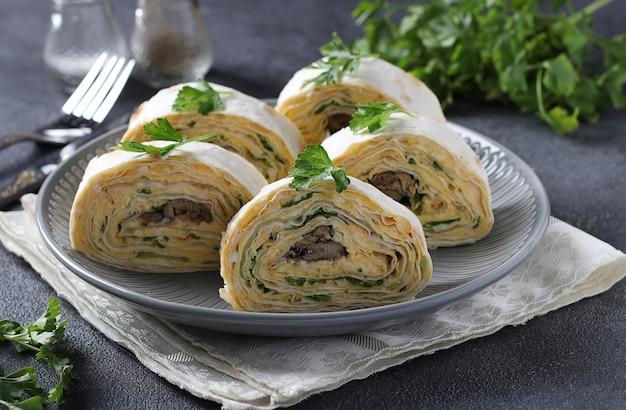 Rotolo di lavash con spratti, crema di formaggio, cetriolo e uova su sfondo grigio scuro