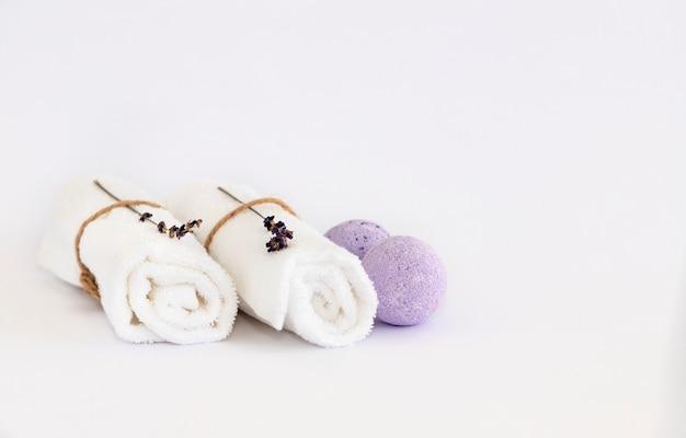Sfera da bagno alla lavanda, asciugamani bianchi con rametti di lavanda