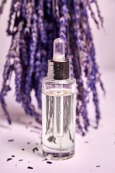 Olio cosmetico di lavanda in un flacone contagocce con pepit di vetro e fiori di lavanda secchi sul tavolo di legno