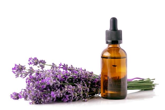 Olio essenziale di lavanda in una bottiglia e un bouquet di lavanda in fiore su uno sfondo bianco isolato.