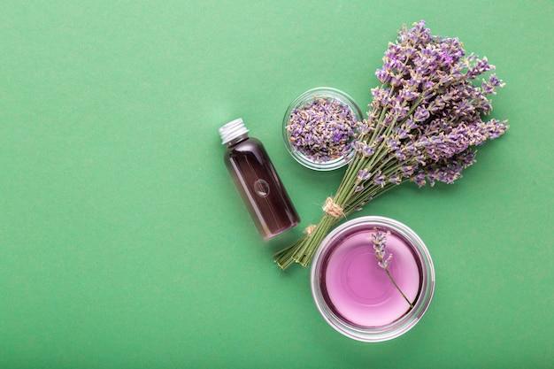 Bottiglia di olio essenziale di lavanda su sfondo di colore verde aromaterapia fresca di fiori di lavanda