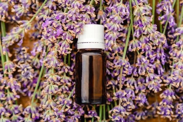 Bottiglia di vetro di olio essenziale di lavanda su fiori di lavanda freschi. cosmetico per la cura della pelle alla lavanda. prodotti di bellezza naturali termali. erbe farmacie piatte per il trattamento dell'aromaterapia.