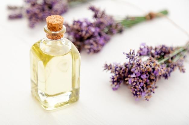 Bottiglia di vetro dell'olio essenziale della lavanda sui fiori freschi della lavanda della tavola rustica di legno bianca. trattamento aromaterapico, cosmetici naturali termali, erbe aromatiche alla lavanda.