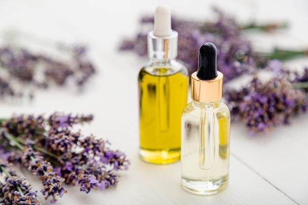 Olio essenziale di lavanda bottiglie di vetro contagocce siero su tavolo di legno bianco fiori di lavanda freschi