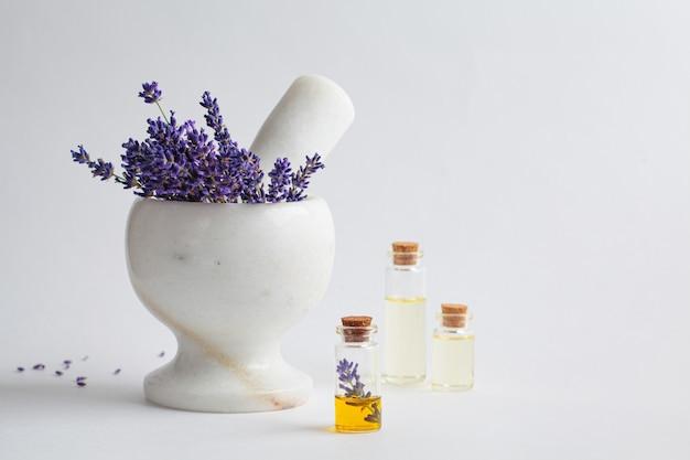 Olio essenziale di lavanda in piccole bottiglie di vetro e fiori di lavanda in un mortaio, sfondo bianco.