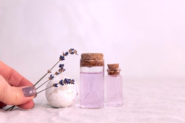 Olio essenziale di lavanda con bouquet di lavanda essiccata sul tessuto di lino.