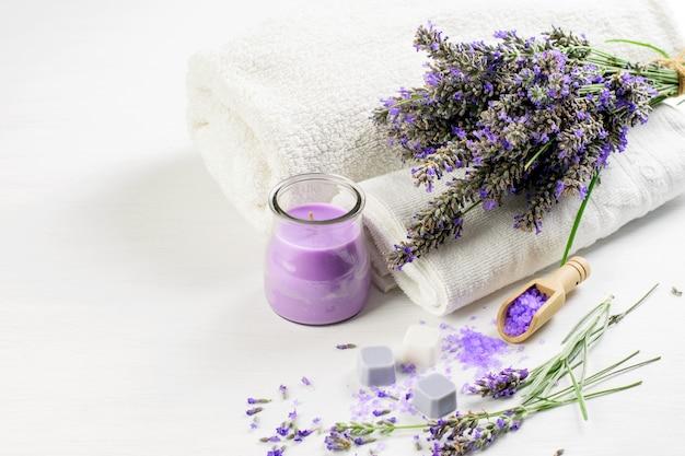 Fiori di lavanda e sapone alla lavanda spa e sale, asciugamani bianchi. aromaterapia spa, concetto di assistenza sanitaria.