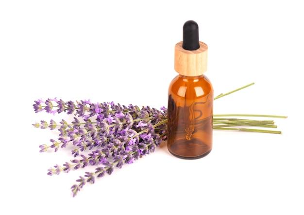 Fiori di lavanda con bottiglia di vetro per olio essenziale, isolato su sfondo bianco. erbe medicinali e oli.