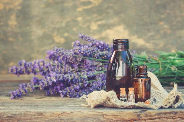 Olio di lavanda in diverse bottiglie su fondo di legno.
