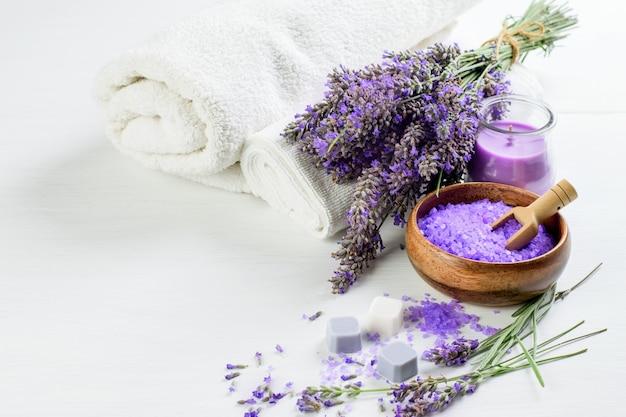 Prodotti alla lavanda per aromaterapia termale: fiori di lavanda, sale, sapone, candela e asciugamani bianchi. assistenza sanitaria, concetto di medicina alternativa.