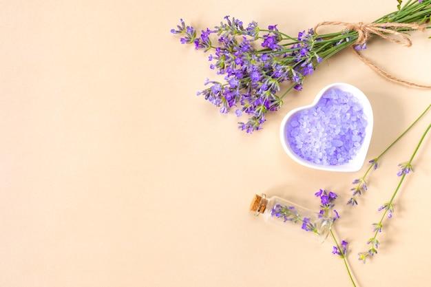 Sale marino alla lavanda in piatto a forma di cuore, bottiglia e rametti di lavanda su fondo beige con posto per il testo. concetto di bellezza