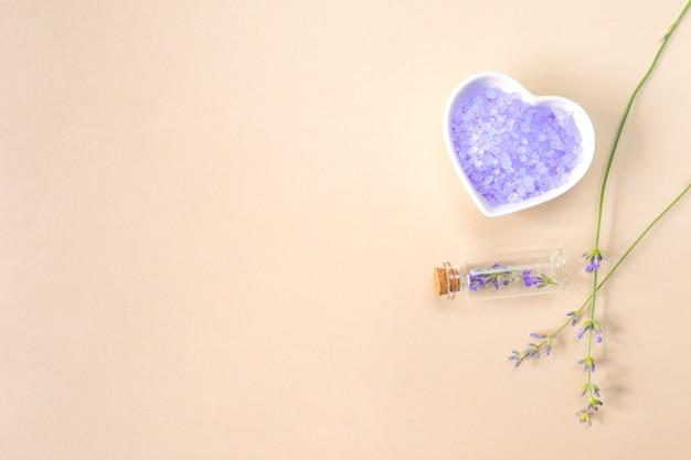 Sale marino alla lavanda in un piatto a forma di cuore, bottiglia e rametti di lavanda su uno sfondo beige con un posto per il testo. concetto di spa