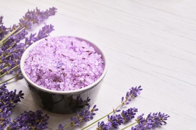 Lavanda spa. fiori di lavanda e sale da bagno in una ciotola su bianco. copia spazio spa concept.