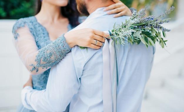 Bouquet da sposa lavanda nelle mani della sposa in abito biancoblublue