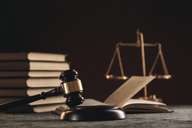Concetto di legge - libro aperto di legge con un martello di legno dei giudici sul tavolo in un'aula di tribunale o in un ufficio delle forze dell'ordine su sfondo nero.