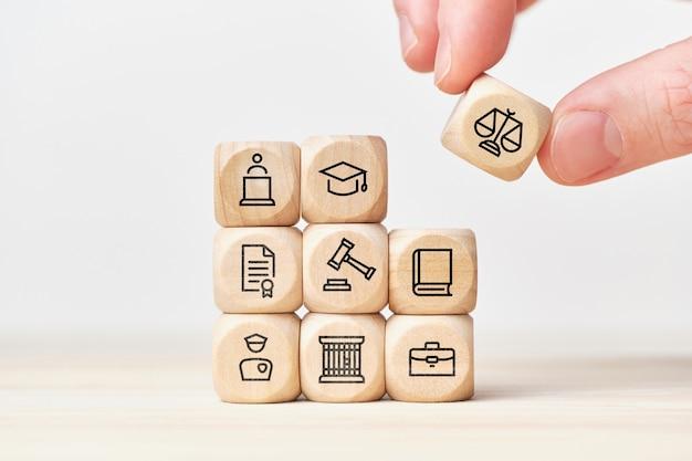 Concetto di costruzione del sistema di applicazione della legge con leggi, tribunali e polizia su cubi di legno.