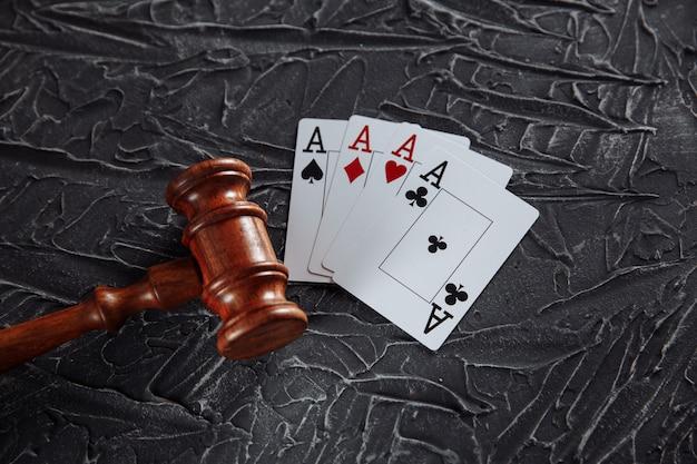 Legge e regole per il concetto di gioco d'azzardo online, martelletto del giudice con carte playng su sfondo grigio.