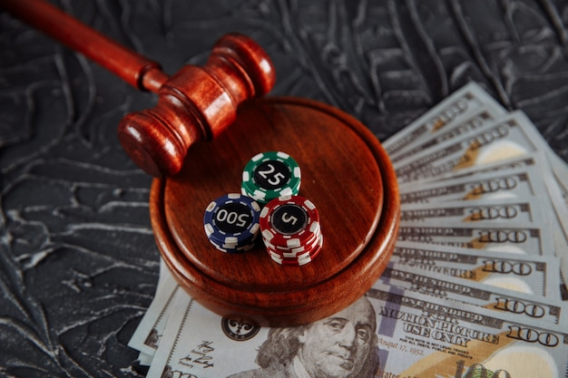 Legge e regole per il concetto di gioco d'azzardo online, martelletto del giudice con carte da gioco e banconote in denaro su sfondo grigio.