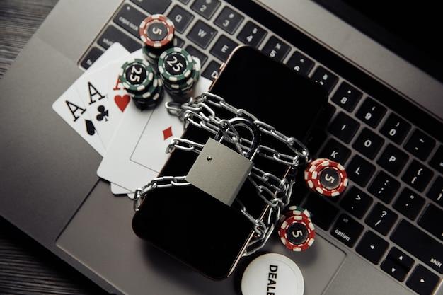 Legge e regole per il concetto di gioco d'azzardo online, smartphone con lucchetto e carte da gioco sulla tastiera del laptop.