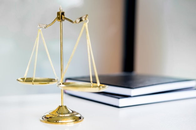 Libro di legge o libri dorati di peso e giallo sul tavolo. simbolo della giustizia
