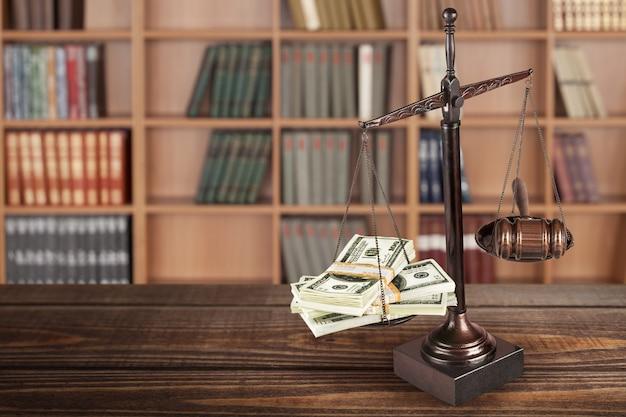 Scale di legge e denaro sullo sfondo della tabella. simbolo di giustizia