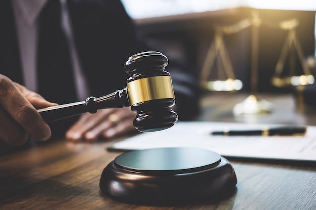 Avvocato o consulente che lavora su un documento e tiene un martelletto in aula di tribunale, giustizia e legge