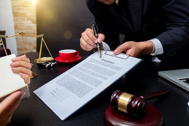 Avvocato particolare di un giudice seduto alla sua scrivania, che studia nuove leggi e normative e prende appunti. messa a fuoco selettiva.
