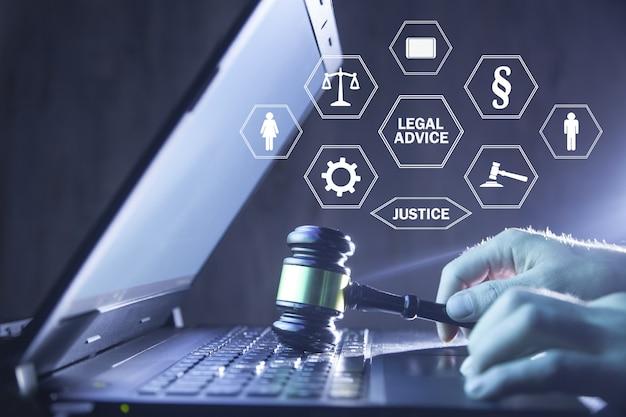 Martelletto della holding dell'avvocato sulla tastiera del computer portatile. consulenza legale