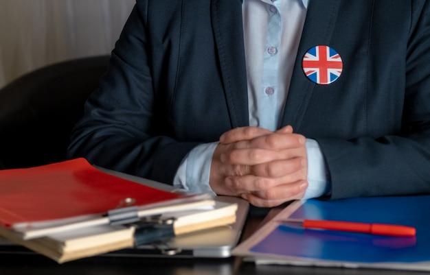 Avvocato o impiegato di ufficio o funzionario pubblico vicino al suo posto di lavoro con la bandiera della gran bretagna su un'icona della giacca