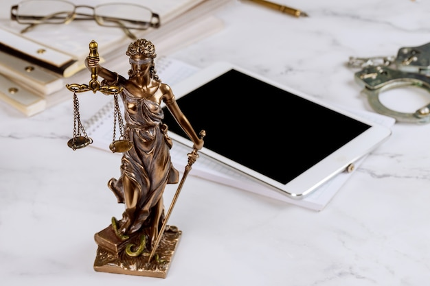 Studio legale statua della giustizia con bilancia e avvocato che lavora su una tavoletta digitale