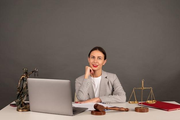 Ufficio dell'avvocato. statua della giustizia con bilancia e avvocato che lavora su un laptop. diritto legale, consulenza e concetto di giustizia
