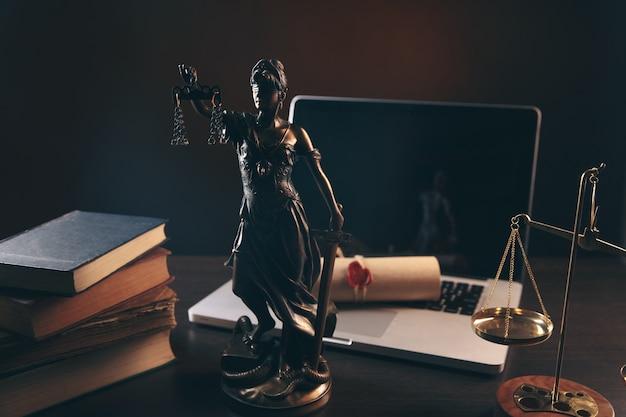 Statua dell'ufficio di avvocato della giustizia con scale e avvocato che lavora su un consiglio di legge legale portatile e concetto di giustizia