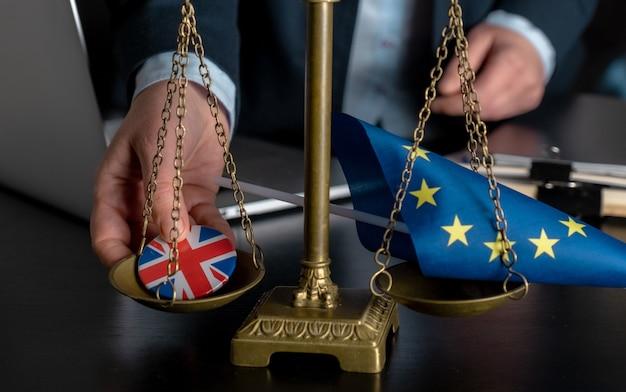 L'avvocato mette sulla bilancia la bandiera dell'unione europea e la bandiera della gran bretagna su un'icona di giacca insieme su una bilancia.