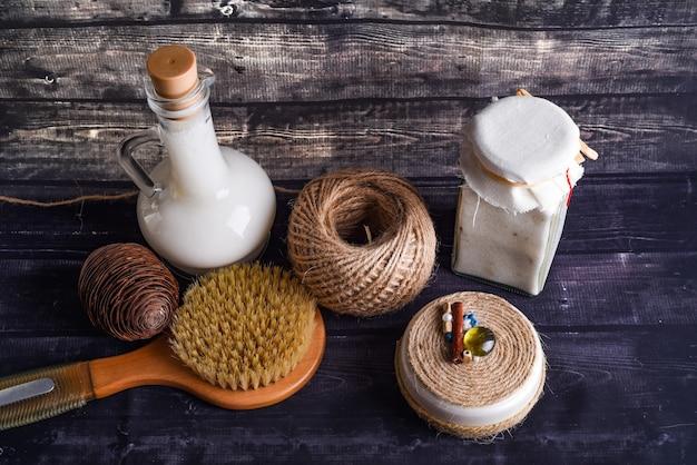 La composizione laica con prodotti per la cura del corpo. un vasetto di crema naturale, una bottiglia di olio di cocco e una moneta di pino