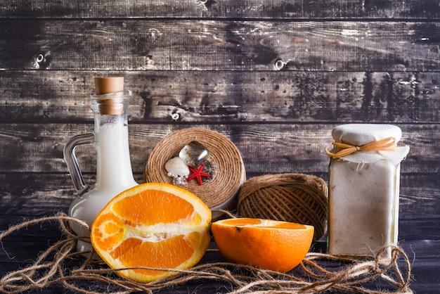 La composizione laica con prodotti per la cura del corpo. un vasetto di crema naturale, una bottiglia di olio di cocco e un'arancia matura