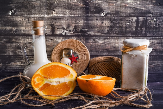 La composizione laica con prodotti per la cura del corpo e spazio per il testo su sfondo di legno scuro. un vasetto di crema naturale, una bottiglia di olio di cocco e un'arancia matura