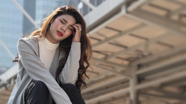 Tempo di sosta. licenziato. donna d'affari licenziata seduta sulle scale dell'edificio per uffici all'esterno. disoccupazione depressa della giovane donna d'affari a causa della crisi del coronavirus. preoccuparti niente lavoro niente soldi. licenziato è stato licenziato.