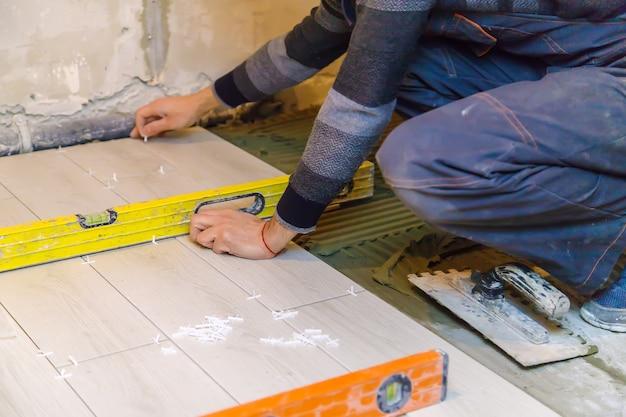 Posare le piastrelle sul pavimento della casa. messa a fuoco selettiva.